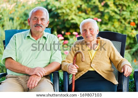 Happy elderly woman in a nursing home with her visitor - her son. - stock photo