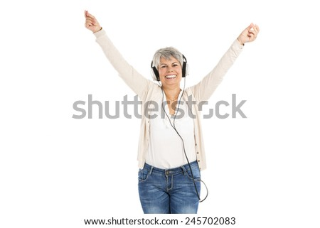 Happy elderly woman listen music with headphones, isolated over white background - stock photo