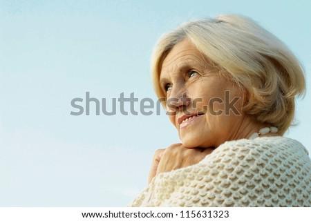 Happy elderly woman posing against the sky - stock photo