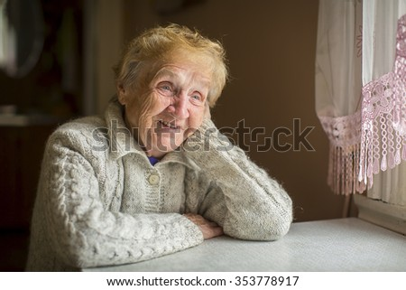 Happy elderly woman sitting at a table near the window. - stock photo