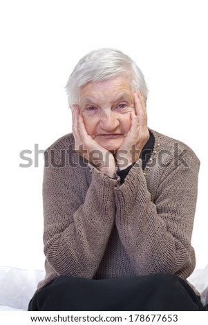Happy elderly wrinkled woman sitting  on the bed - stock photo