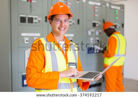 happy electrical technician using laptop in power plant control room - stock photo