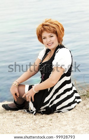 happy elegant middle aged plus size woman resting near sea shore and smiling with beautiful makeup and healthy glossy hair. Rich lady relaxing at beach spring-summer - stock photo