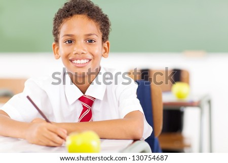 happy elementary schoolboy studying in classroom - stock photo