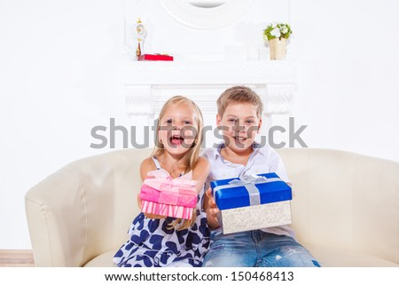 Happy emotional kids with present boxes - stock photo