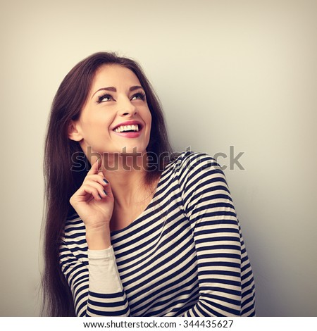 Happy emotional woman thinking and looking up with toothy smiling. Vintage portrait - stock photo