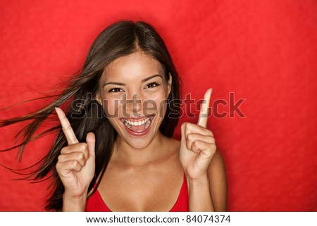Happy energetic woman on red pointing fresh. Candid portrait of cheering beautiful young mixed race Chinese Asian / white Caucasian woman on red background. - stock photo