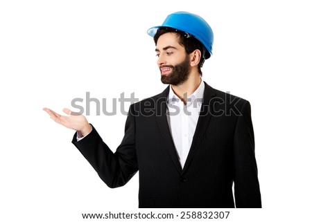 Happy engineer businessman showing empty copyspace on palm. - stock photo