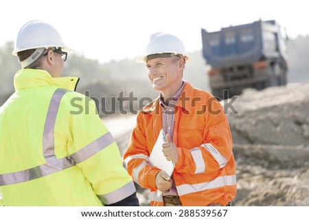 Happy engineer discussing with colleague at construction site on sunny day - stock photo