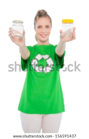 Happy environmental activist wearing recycling tshirt holding jars on white background - stock photo