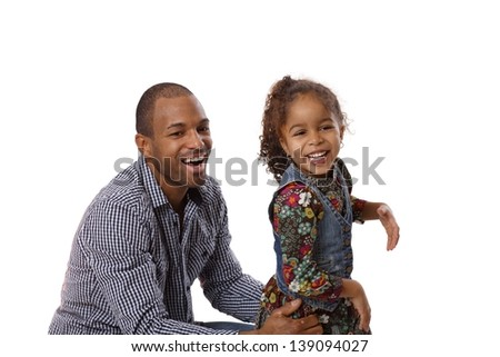 Happy ethnic father and cute little daughter laughing, having fun, father squatting. - stock photo