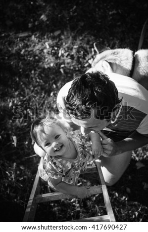 Happy european child climbing the vertical ladder. Father helps and protects his adorable little kid. Playground outdoors. Walk in the fresh air. Daughter, baby, girl. Photo in black and white - stock photo