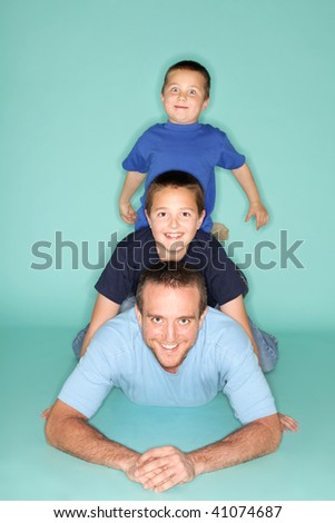 Happy, excited family relaxing together on the floor - stock photo