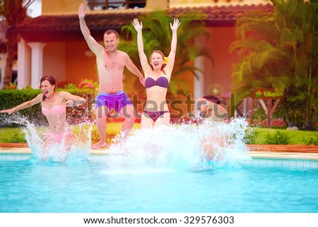 happy excited friends jumping together in pool, summer fun - stock photo