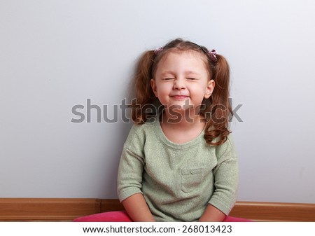 Happy excited girl screwing up her eyes and waiting something good sitting on the floor - stock photo