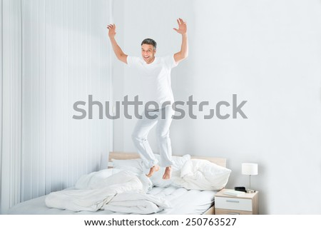 Happy Excited Mature Man Jumping On Bed At Home - stock photo