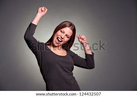 happy excited woman dancing over dark background - stock photo