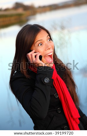 Happy excited woman on cellphone outside by waterside. Beautiful mixed race caucasian / asian woman, - stock photo