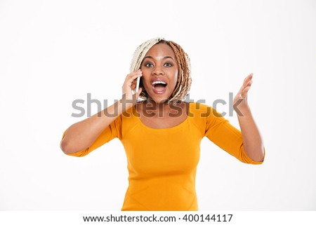 Happy excited young african american woman talking on mobile phone over white background - stock photo