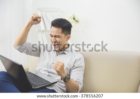 happy excited young man with laptop at home sitting on a couch - stock photo