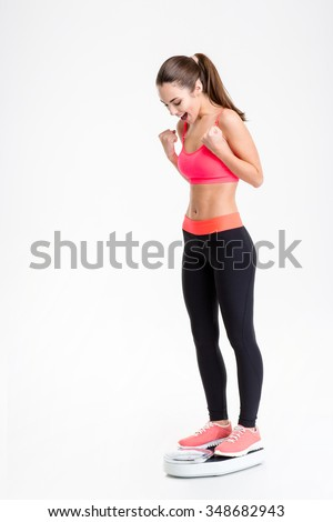 Happy excited young sportswoman in pink top and black leggings standing on weigh scale over white background - stock photo