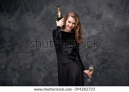 Happy excited young woman in black dress with bottle and glass of champagne over grey background - stock photo
