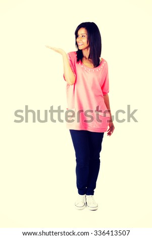 Happy , excited young woman presenting copy space on her palm - stock photo