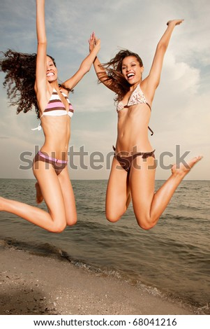 Happy excited young women in bikini jumping on beach - stock photo