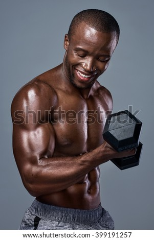 Happy exercise fitness man in studio with strong fit muscular body - stock photo