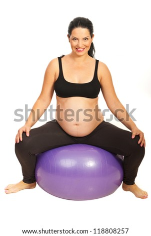 Happy expectant woman sitting on pilates ball isolated on white background - stock photo