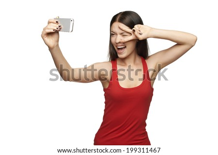 Happy expressive young woman posing while taking pictures of herself through cellphone, over white background - stock photo