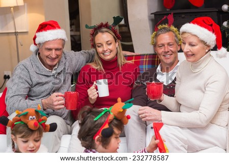 Happy extended family enjoying coffee at christmas time at home in the living room - stock photo