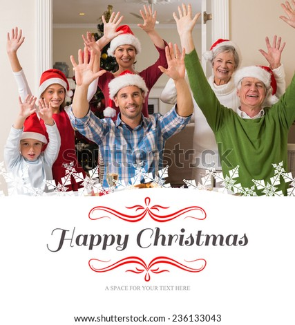 Happy extended family in santa hat cheering at camera against border - stock photo