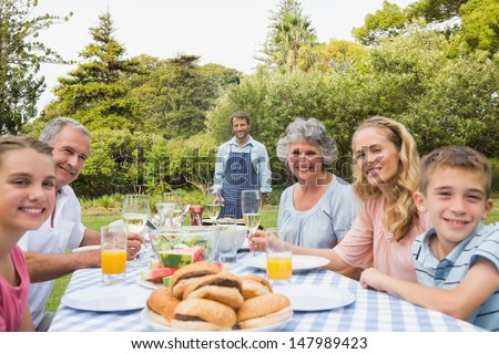 Happy extended family waiting for barbecue being cooked by father smiling at camera - stock photo