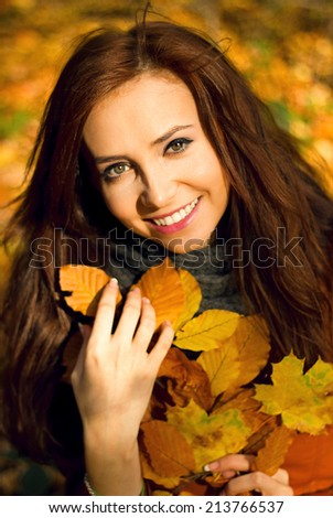 happy fall woman smiling joyful and blissful holding autumn leaves outside in colorful fall forest - stock photo