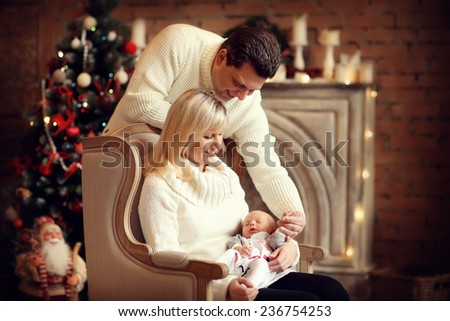 Happy family: a beautiful young blonde woman sitting in a chair and holding her cute newborn baby and her smiling husband in white clothes against a decorated twinkling Christmas tree. New Year's Eve. - stock photo
