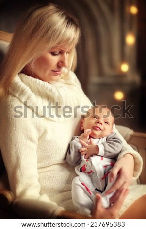 Happy family: a close up portrait of a beautiful young blonde woman in white clothes sitting in a chair and holding her cute newborn baby on her knees. - stock photo