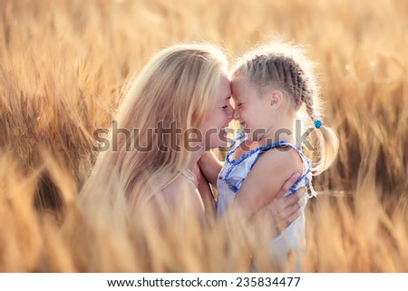Happy family: a young beautiful pregnant woman with her little cute daughter walking in the wheat orange field on a sunny summer day. Parents and kids relationship. Nature in the country. - stock photo