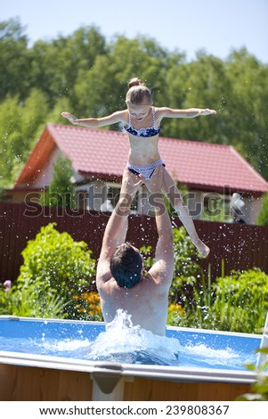 Happy family, active father with little child, adorable toddler girl swim in the pool - stock photo