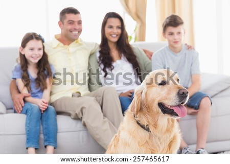 Happy family and dog watching TV together in living room - stock photo
