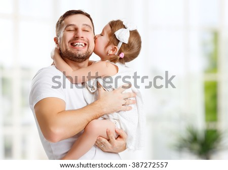 happy family and father's day. child daughter kissing and hugging dad - stock photo