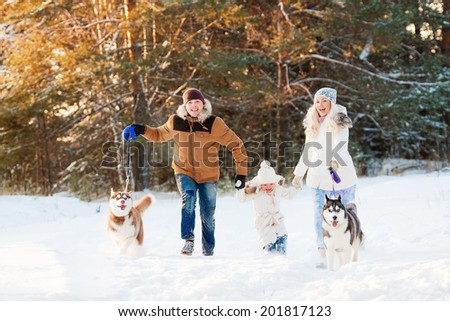 Happy family and husky dog in winter park - stock photo