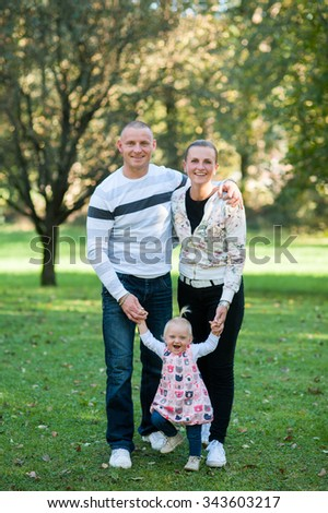 Happy, family are standing and walking outside in the park on a sunny day. - stock photo