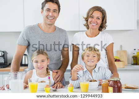 Happy family at breakfast in kitchen - stock photo