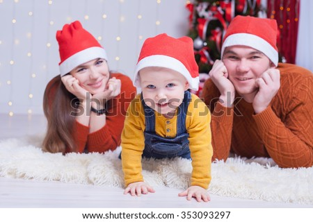 Happy family at Christmas eve lying together near decorated tree at living room, home. They dressed in winter pullover and Santa hat. Father, mother and baby looking at camera. New Year. - stock photo