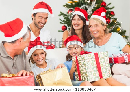Happy family at christmas swapping gifts on the couch - stock photo