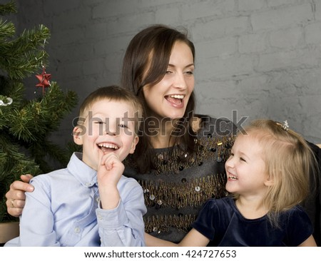 happy family at christmas tree sitting home smiling, waiting for father at holiday evening - stock photo