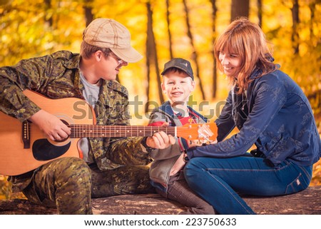 happy family at fall forest playing and singing song - stock photo