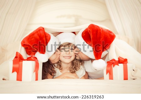 Happy family at home. Mother, father and child with Christmas gift. Xmas holiday concept - stock photo