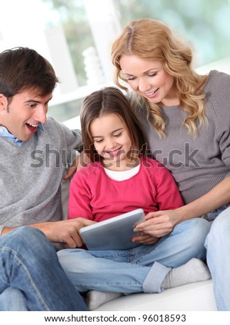 Happy family at home using electronic tablet - stock photo